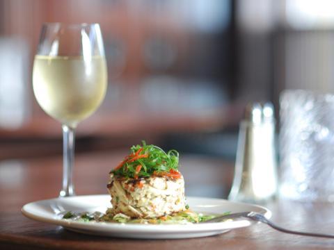 Un atractivo emplatado y una copa de vino en un restaurante de Nueva Orleans