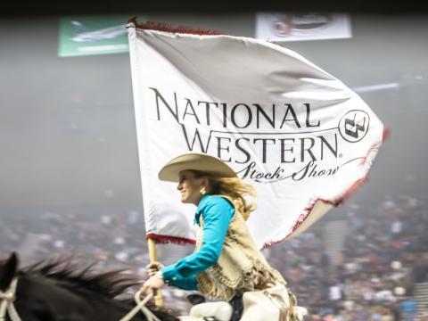 Montando a caballo con la bandera del National Western Stock Show & Rodeo de Denver