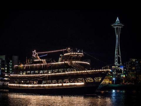 Un barco decorado flotando en frente de Space Needle durante Argosy Christmas Ships & Bonfires
