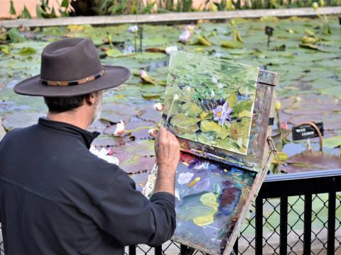 Un artista pintando los lirios de agua en el Civic League Park durante la EnPleinAirTEXAS National Competition & Cinch Roping Fiesta en Texas